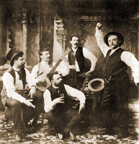"Chueca (right) with Valverde (cross-legged), Felipe P�rez y Gonz�lez (hat), Juli�n Romea (guitar) and Ruiz de Arana, celebrating the triumph of ""La Gran V�a"" in Seville (1886)"